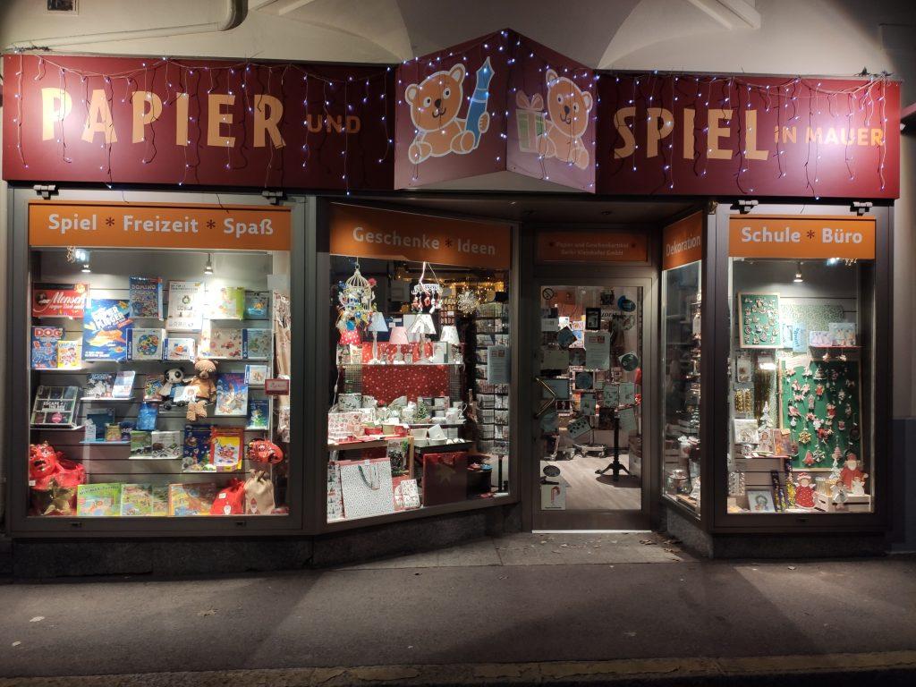 Auf diesem Bild sieht man das Portal des Geschäfts in der Nacht.